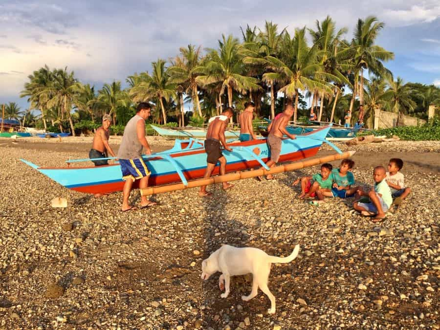 Men carry The Hang Out Express onto the rock beach on mainland Malay, across the channel from Boracay.