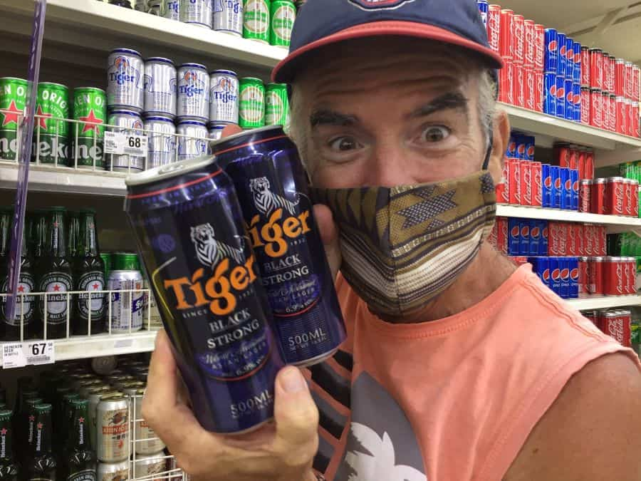 Tedly holds Tiger cans of beer in the store, and smiles because it's a 'beer deal'.