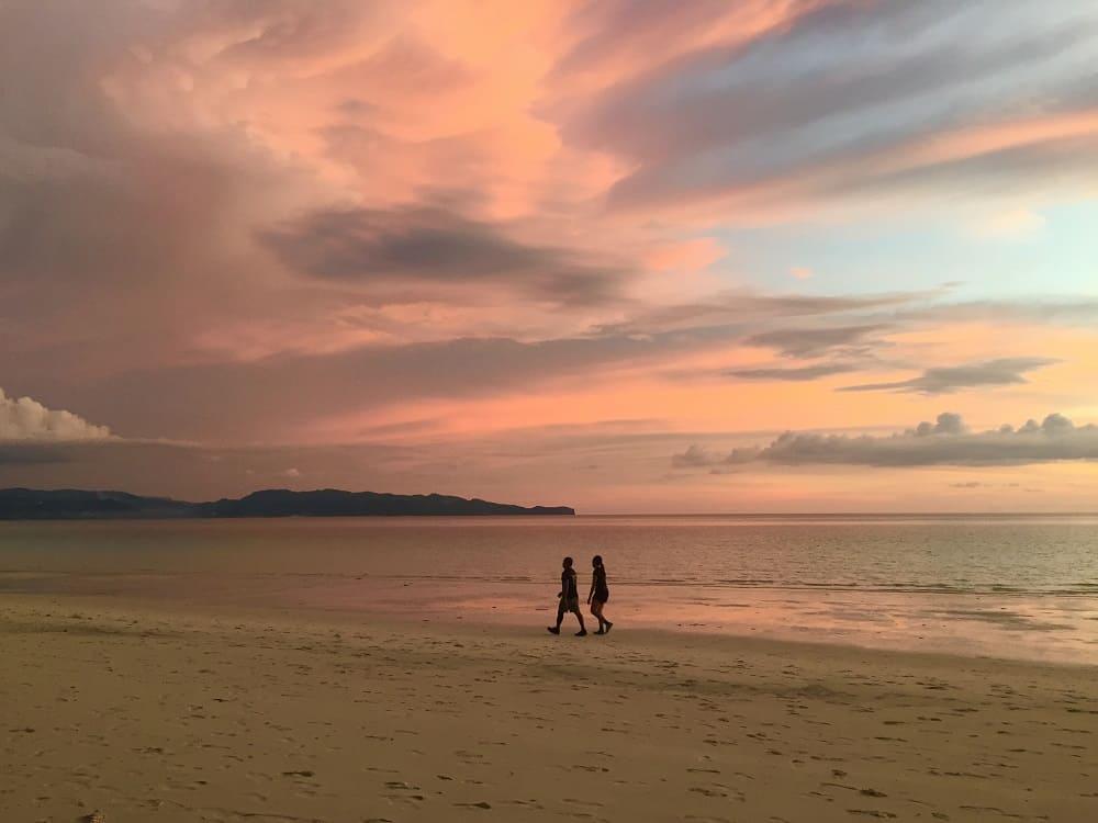 tropical paradise boracay sunset with couple walking the beach