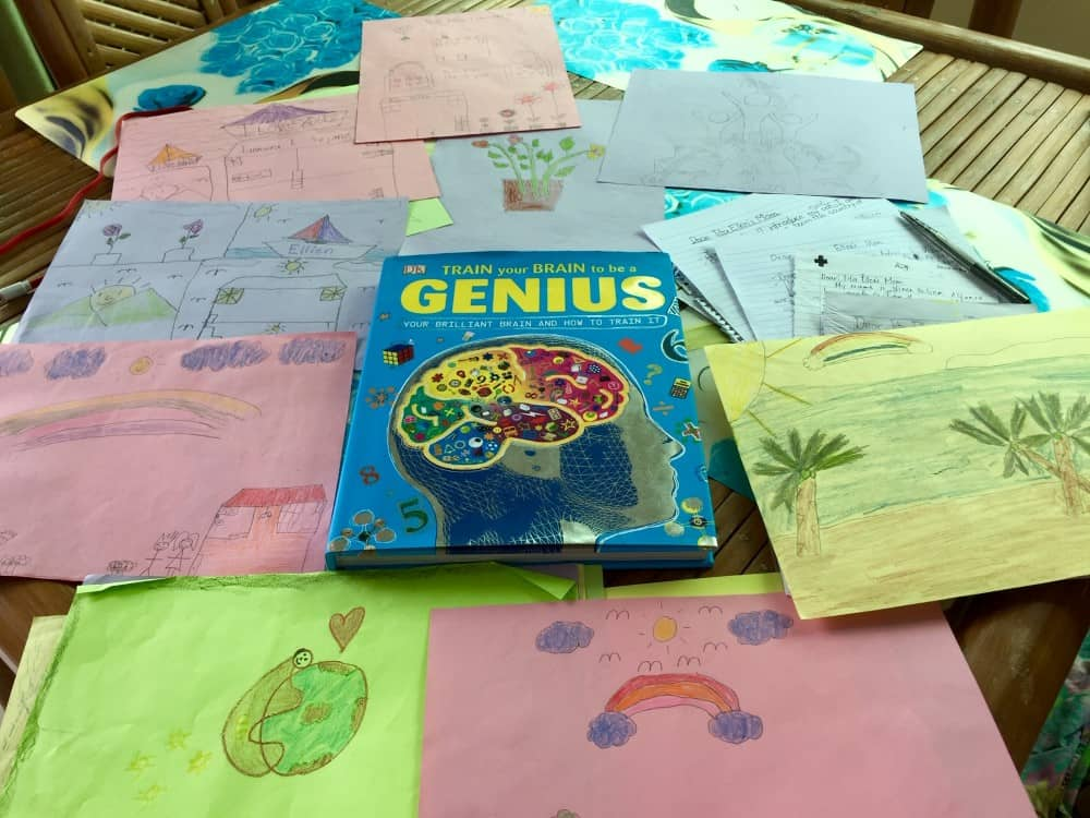 """A book titled """"Train your Brain to be a Genius"""" along with homework assignments and children's drawings spread out on a table."""