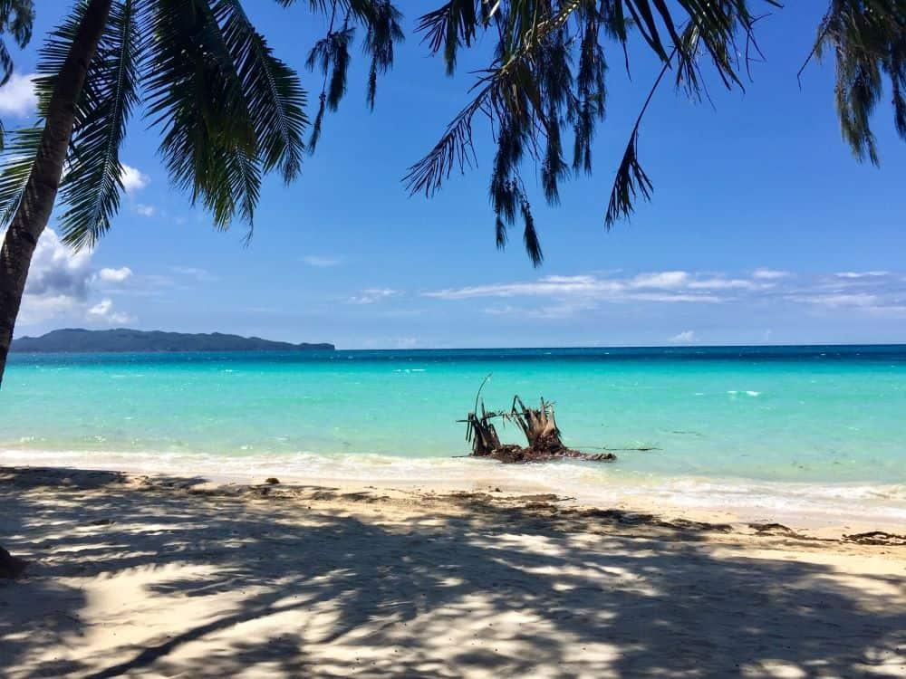 empty white beach with fallen tree debris on opening day of boracay island