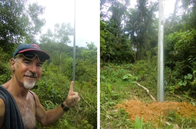 Tedly smiles in front of an upright power pole- progress in the Ati electricity hookup effort.