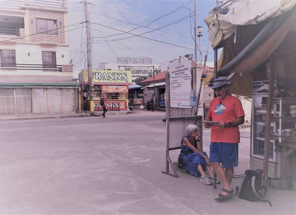 Mom Diane sits on the base of a sign as Theo looks for a place to stay when Earth Vagabonds became stranded in Malay Municipality in the Philippines due to the pandemic.