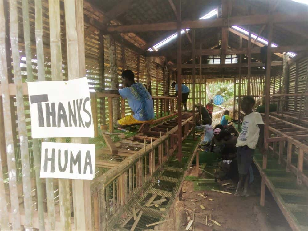 Ati workers construct the new henhouse in 2020 with materials bought by donated funds from overseas.