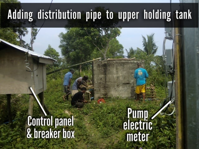 Ati workers add distribution pipe to the upper holding tank, control panel and electric meter also pictured.