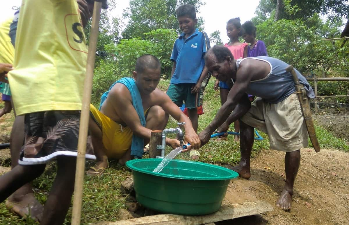 Ati men fill tub with water from the new pump installed by Earth Vagabonds and overseas donors in Malay, Aklan, Philippines.