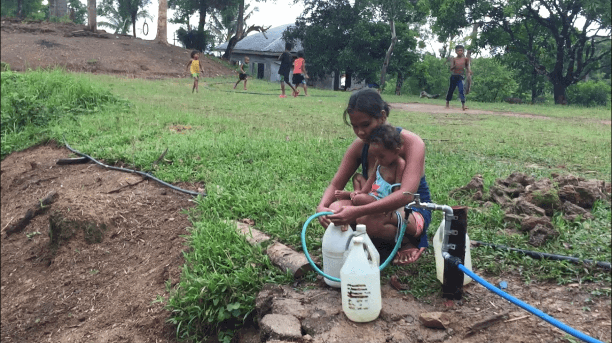 An Ati woman uses the new water spigot in Malay, Aklan, Philippines.