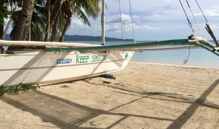 """A Philippine sailboat with the name, """"Keep Smiling"""" sits on White Beach, Boracay Island, Malay, Aklan, Philippines."""